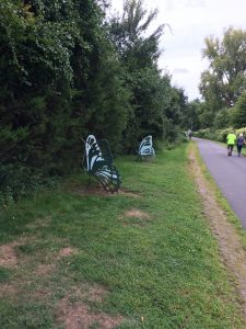 Iron benches shaped like butterflies, on a grassy area by paved recreation trail, with bushes and trees to the side.