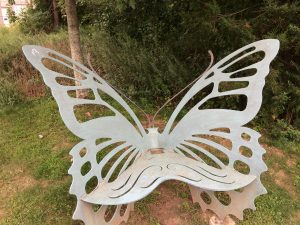 Frontal view of a bench shaped like a butterfly, in front of some bushes.