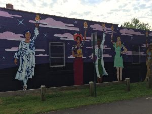 Mural on the side of a building, depicting five women of different ages, races, and ethnicities, each holding a burning torch aloft in one hand.