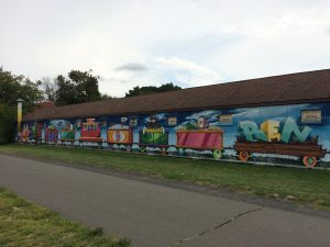 Mural depicting eight joined train cars, with different items in each car.  The last one is carrying large letters spelling the name Ben.