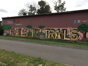 "Mural on the side of an industrial building, depicting the words ""Rails to Trails"", with painted trees between the words, and painted vines winding around the letters."