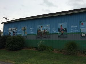 Mural on the side of a building, depicting different types of trail users (3 cyclists, a jogger, and a rollerblader).  There is some landscaping at the base of the wall.