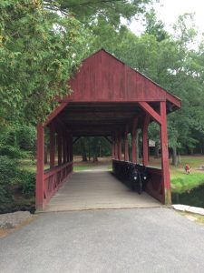 Red, wooden, covered bridge over a small stream, with trees and picnic areas on the other side.