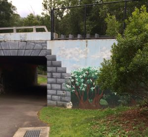Mural of a flowering bush as well as painted stones on the concrete wall of a bike tunnel entrance.