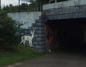 Mural of a deer and small cityscape, as well as painted stones on the concrete wall of a bike tunnel entrance.