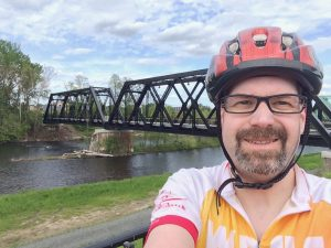 Selfie of Sean with bike bridge and river in background