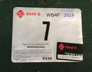 "Rectangular ride or race bib with the brand ""Road ID"", and the number seven on it.  Also labeled as WB4F 2019."
