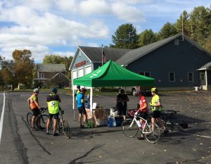 Food and water table under a canopy, with half a dozen cyclists around it.  This is in a parking lot, with the Guilford fire station in the background.