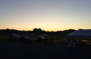 Sunrise in background, with cars and the edge of a canopy in front of a field.