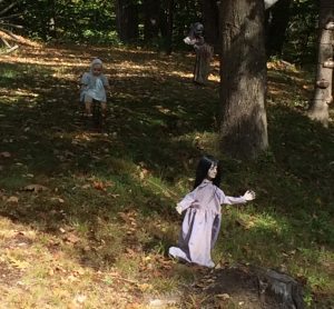 Close view of 2 creepy dolls on lawn, in the shadow of some trees.