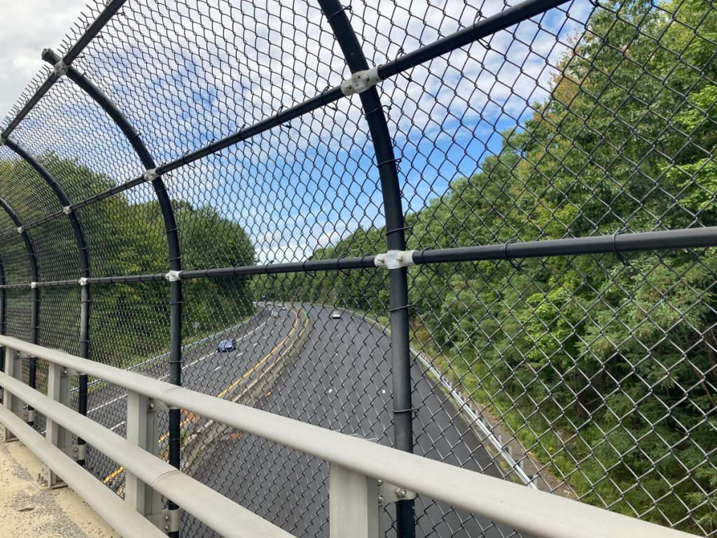 Freeway below, seen from an overpass, looking through chain-link fence.  Trees line the expressway.