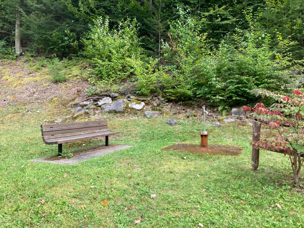 Wooden bench near a water spigot on a rusty base, in a grassy area with bushes and trees behind.