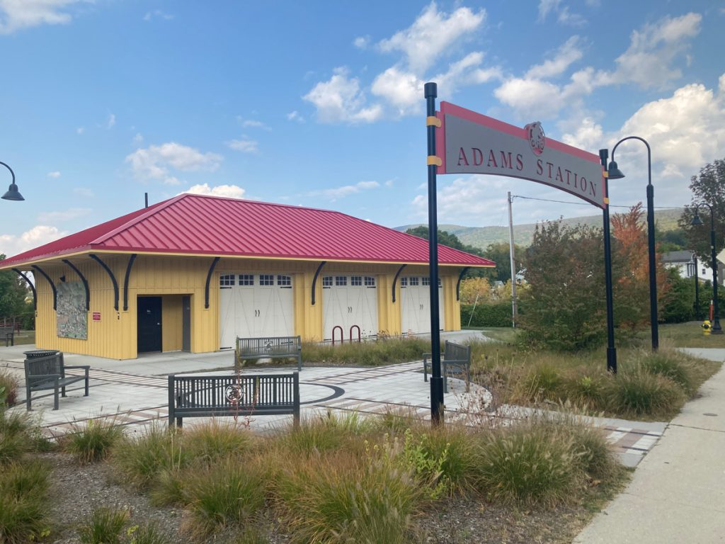 "Old train depot building, painted yellow with a red metal roof.  A high sign in front of the building reads ""Adams Station"", and there are sidewalks, benches, and small plants around."