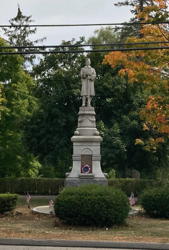 "Stone monument with a statue of a man at the top.  Lettering on the base reads ""Argonne"".  There are bushes, trees, and grass around the monument."