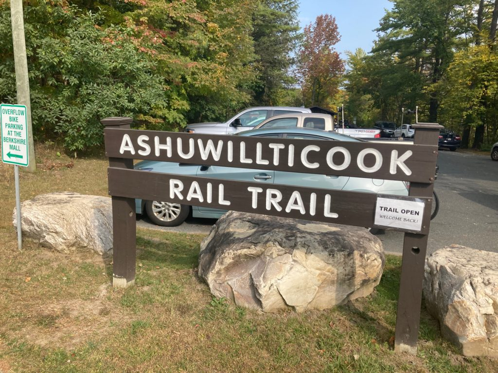 "Wooden sign with white lettering reading ""Ashuwillticook Rail Trail"" with large rocks around the sign posts.  There are parked cars and trees behind it."