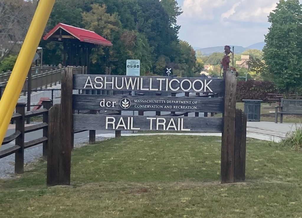 "Wood sign with carved, white-painted letters reading ""Ashuwillticook Rail Trail - Massachusetts Department of Conservation and Recreation"".  Around the sign are grass and trees, and some paved trail surface with a wooden fence."