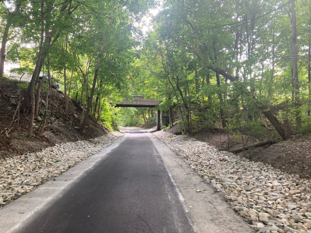 Looking along paved trail with rock beds on each side, then further flanked by trees.  Up ahead there is a bridge over the trail for a road.