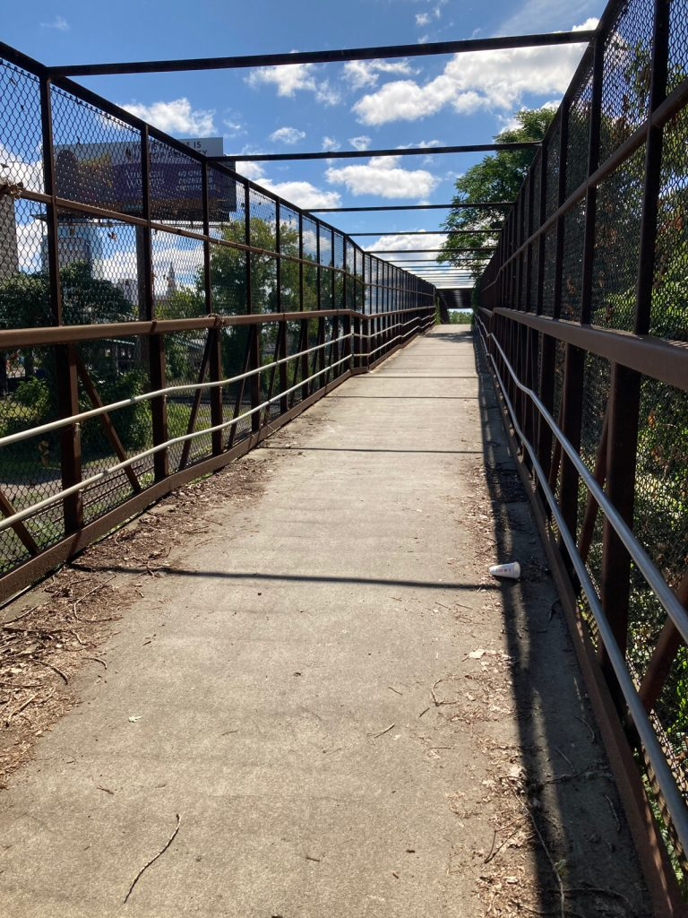 Looking along bike and pedestrian bridge with a concrete deck and metal frame with chainlink walls