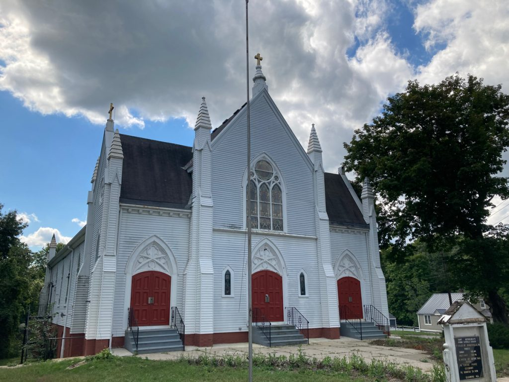 A large, white church building with 3 sets of red double-doors