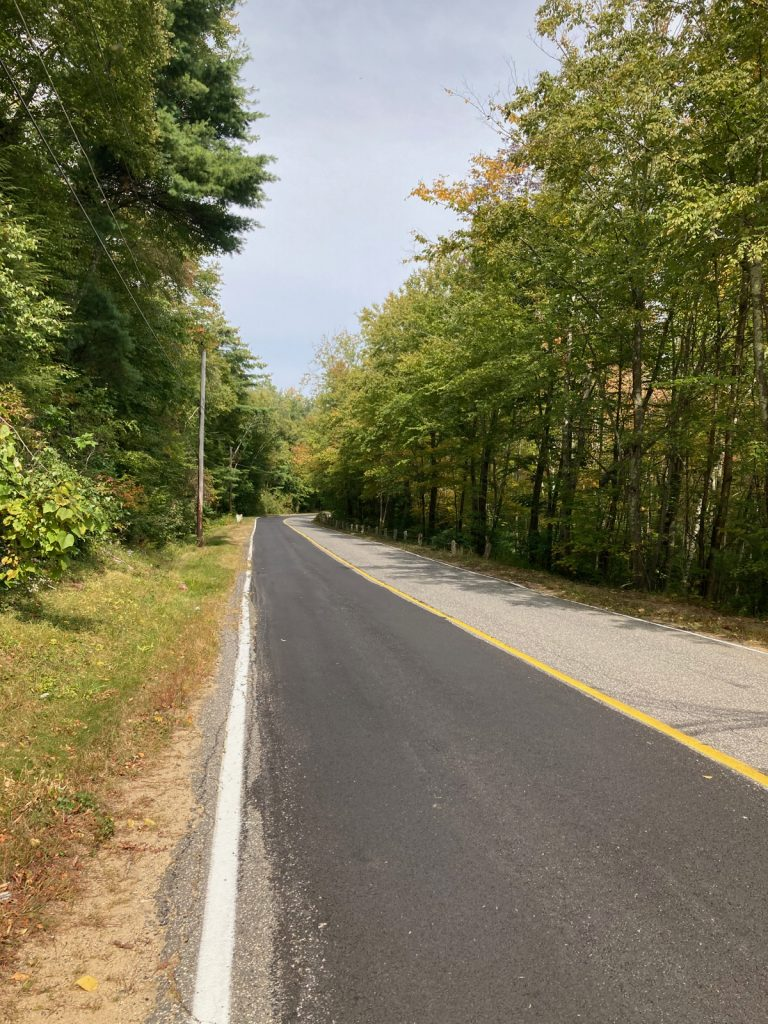 Stretch of road with one lane of dark blacktop, and the other lane lighter in color.  There are trees on each side of the road.