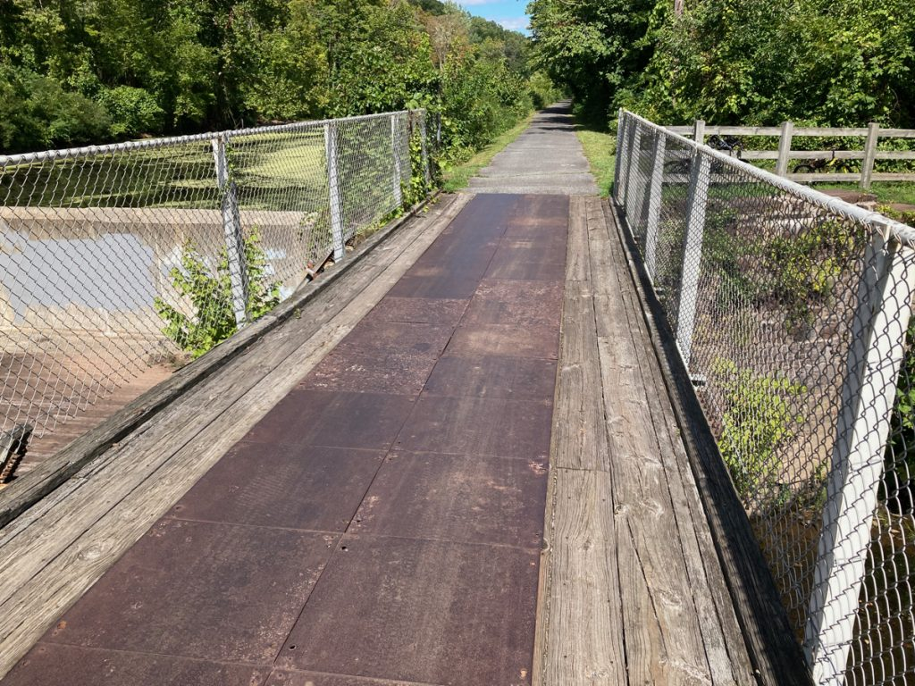 Looking along bike trail bridge with wood and metal deck, and chain link fence on either side.