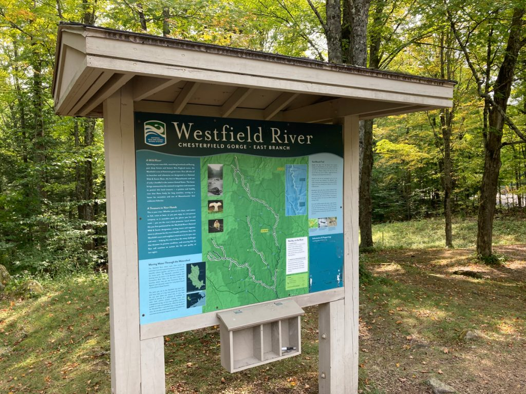 Large signboard with signs about the Chesterfield Gorge on the Westfield River, East Branch.  Woods can be seen behind the board.