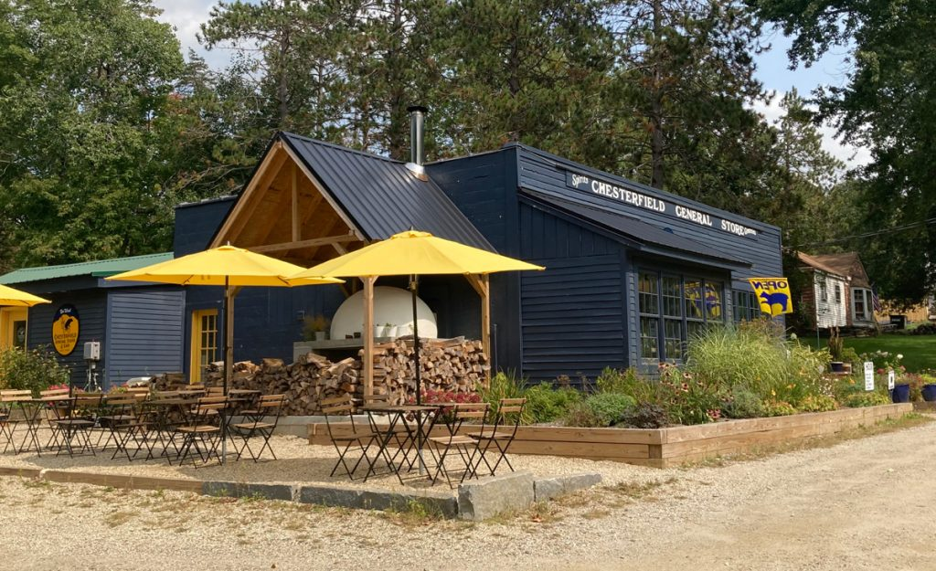Building painted dark blue, with tables and chairs outdoors for dining - there are yellow umbrellas over the tables.  In front of the place is a dirt parking lot, and there are trees behind.