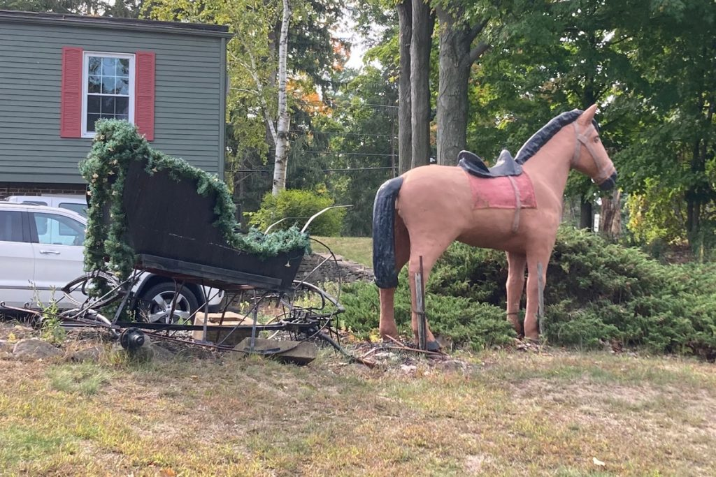 Horse figure on a lawn in front of a parking lot, with an ivy-covered cart or sleigh hitched up to it.  A part of a building is in the background.