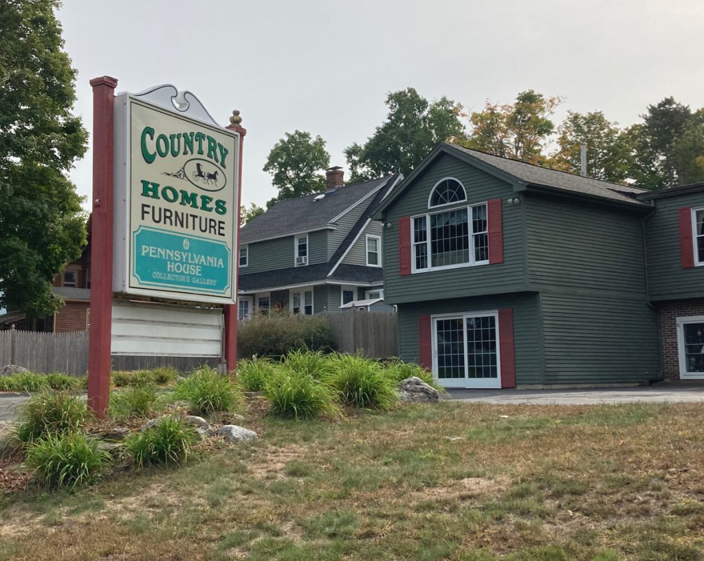 "Large sign reading ""Country Homes Furniture - Pennsylvania House Collector's Gallery"".  The sign is among some small plants and grass, with a parking lot and dark green building in the background."