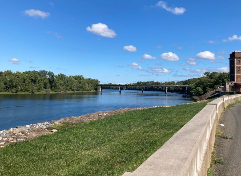 River toward left of photo, with grass and a concrete wall in foreground, there is a bridge crossing the river in the distance, plus blue sky with small clouds
