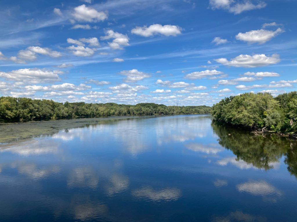 View of river with trees on either side, and reflections of clouds in water.