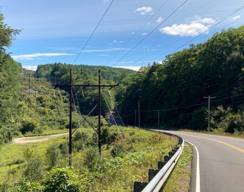 Looking downhill with a road on the right, grass and brush on the left, and some electric wire towers stretching into the distance, heading over a tree-covered hill (through a gap in the trees on the hill).