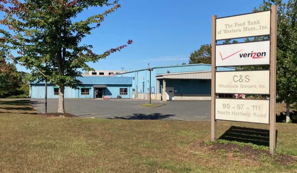 Blue building with parking lot in front of it, one tree in foreground with grass and a set of signs for different businesses.