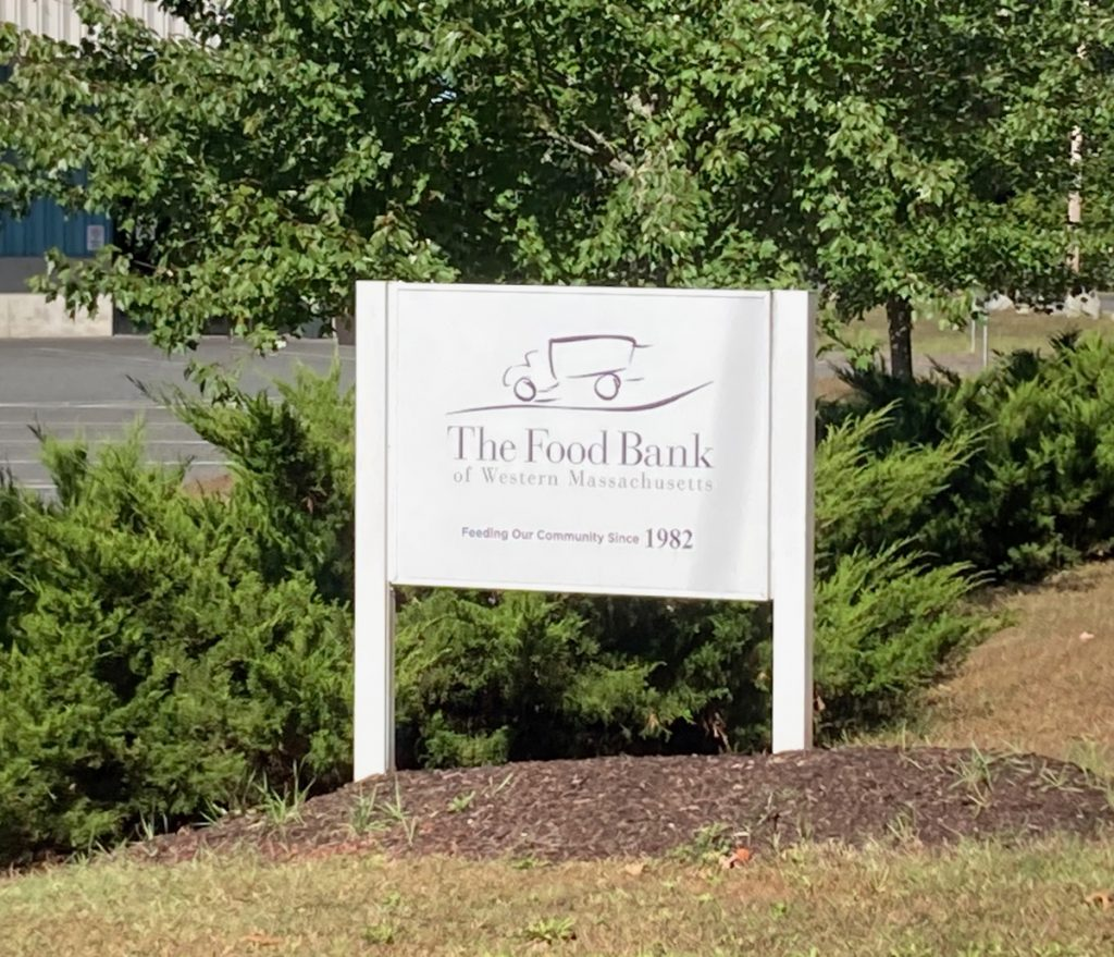 "White wooden sign with text reading ""The Food Bank of Western Massachusetts"" and ""Feeding our community since 1982"", as well as the Food Bank's logo.  The sign has shrubs and trees behind it, as well as a bit of parking lot."