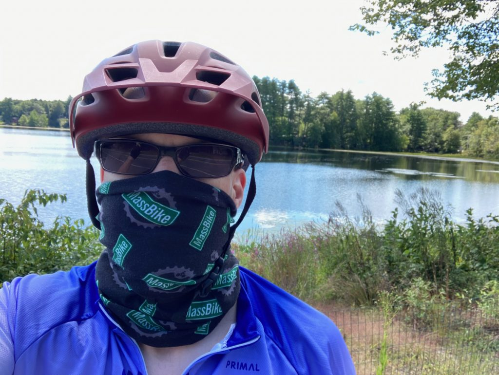 Selfie of Sean, wearing a neck gaiter over nose and mouth, and wearing sunglasses and bike helmet, in front of a lake, trees in background