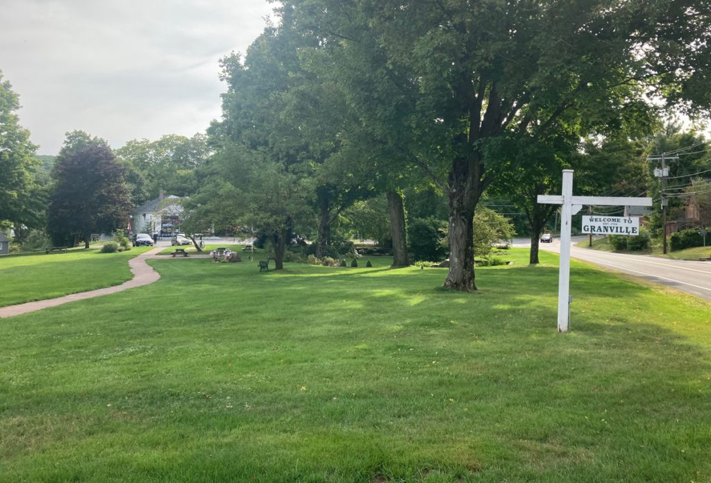 "Town common featuring large field of grass, several trees, and a walking path.  A wooden sign reads ""Welcome to Granville"""