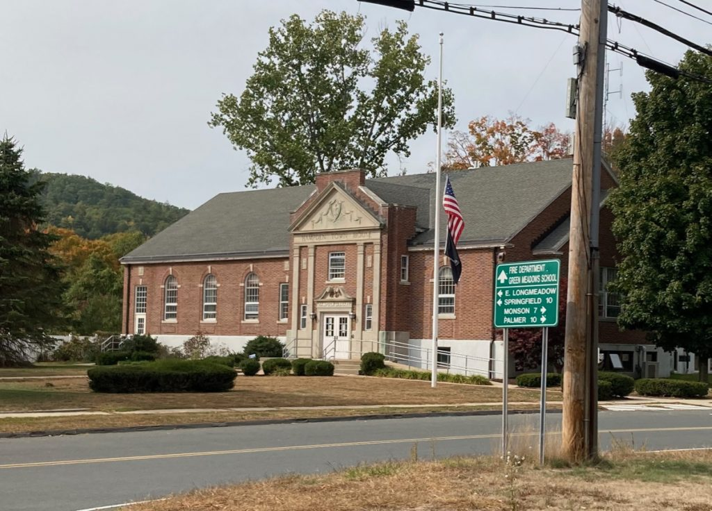 "Brick building that reads ""Hampden Town House"" on the front, with a lawn in front of it, and a flagpole with the US flag at half staff.  There are a few large trees around, and a street running by the building."