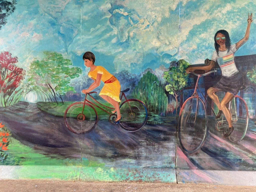 Mural panel depicting cyclists on a recreation trail, one of them waving to the viewer