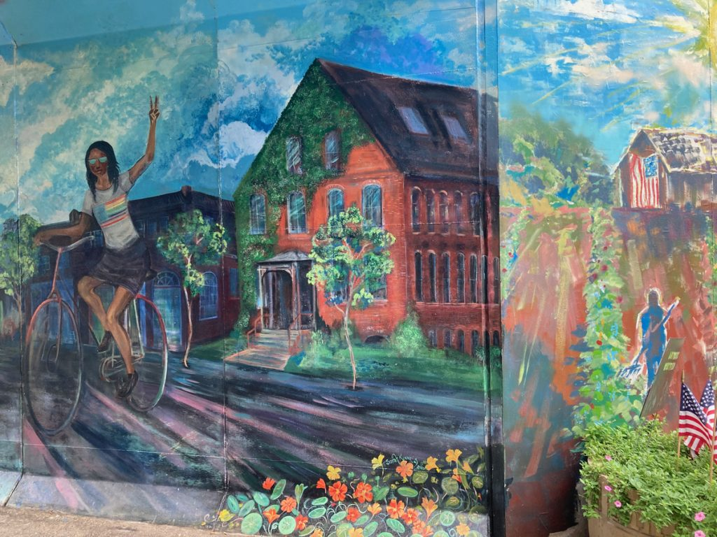 Mural panel depicting waving cyclist and a house covered in ivy