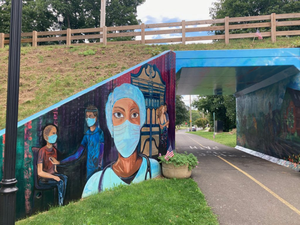 Tunnel under bike path, with a mural to the left of the entrance, depicting health care workers wearing masks