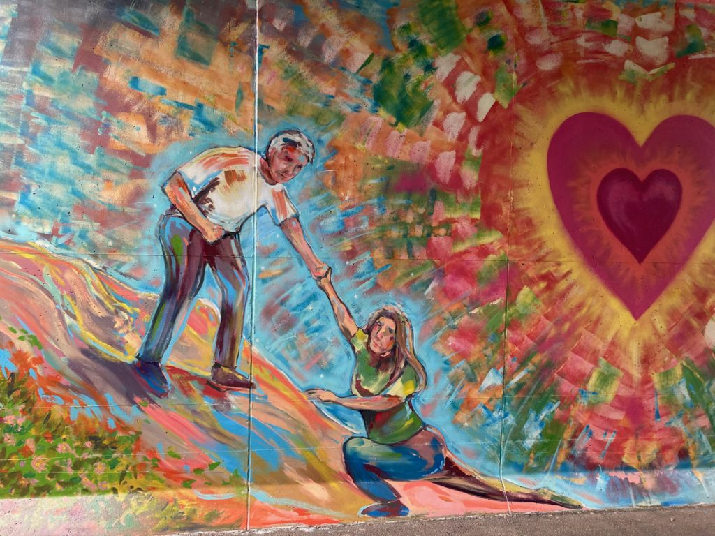 Mural depicting one person helping another up, next to a lage red heart that is glowing and radiating color