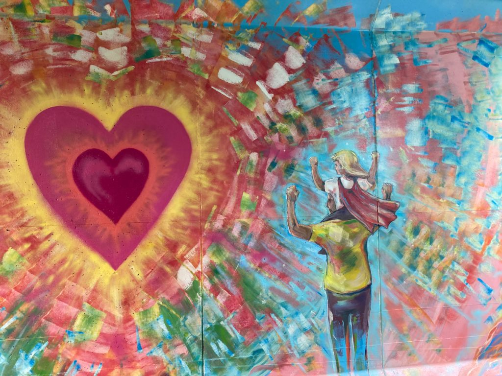 Mural depicting large red heart that is radiating color, with an adult facing it, and a child on the adult's shoulders.  Their hands are raised in the air.