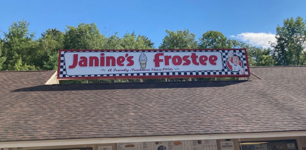 "Sign on a roof of building, which reads ""Janine's Frostee"", with a picture of a soft-serve cone."