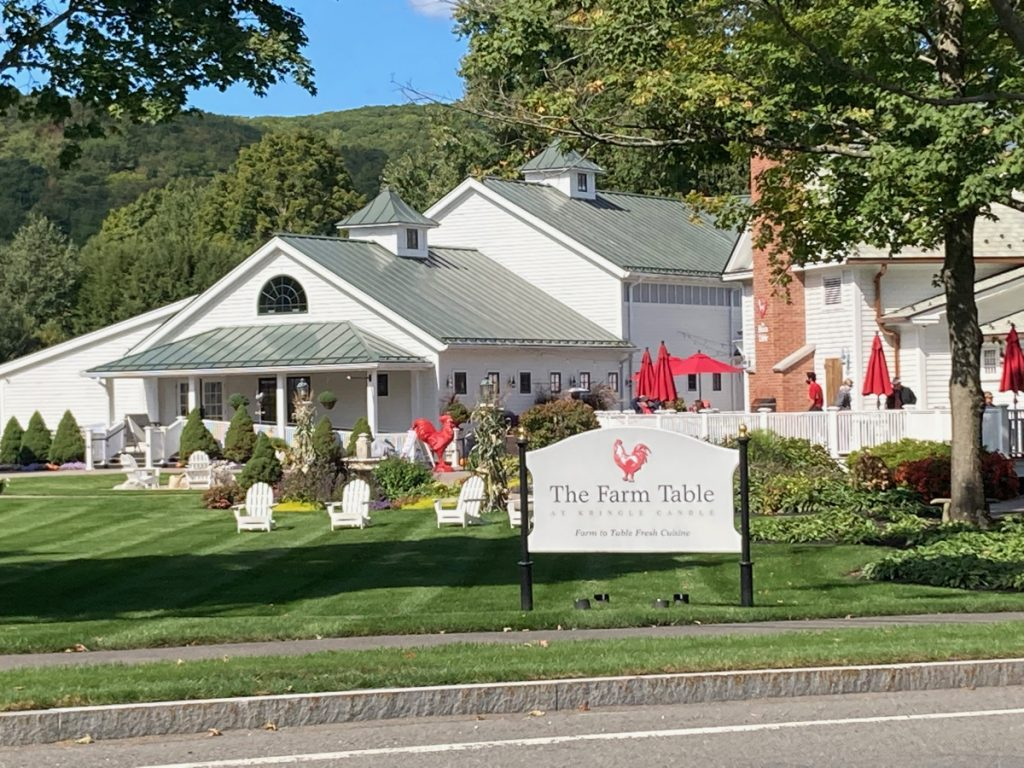 "White building with flowers and other landscaping in front of it, as well as a red rooster statue.  A sign in the foreground (by the roadside) reads ""The Farm Table at Kringle Candle"", and has a red rooster logo."