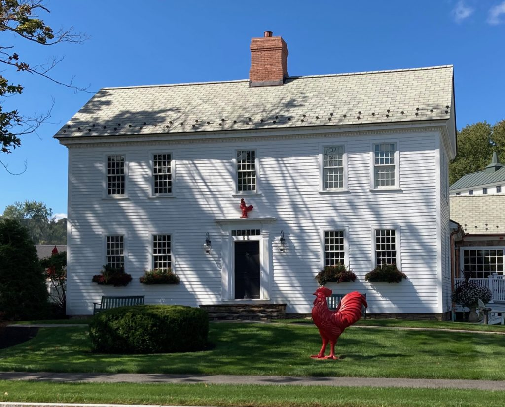 Two-story white house with a red rooster statue on the lawn in front of it.