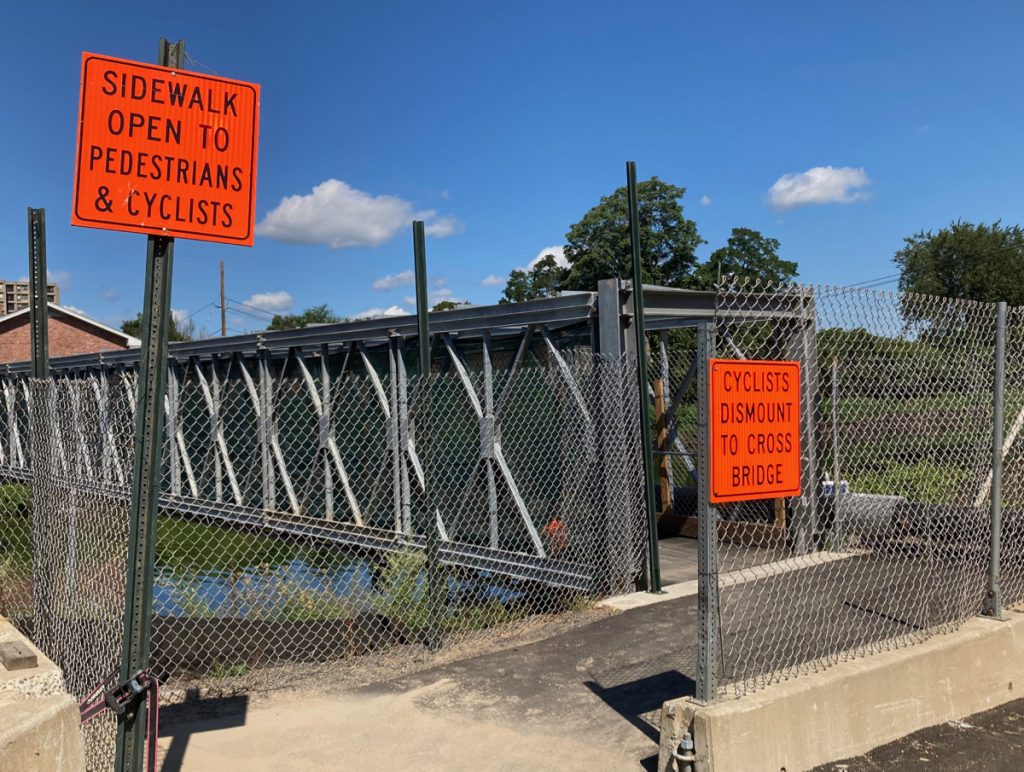 "Entrance to temporary walking bridge, signs read ""bridge for pedestrians and cyclists only"" and ""cyclists must dismount before crossing bridge"""