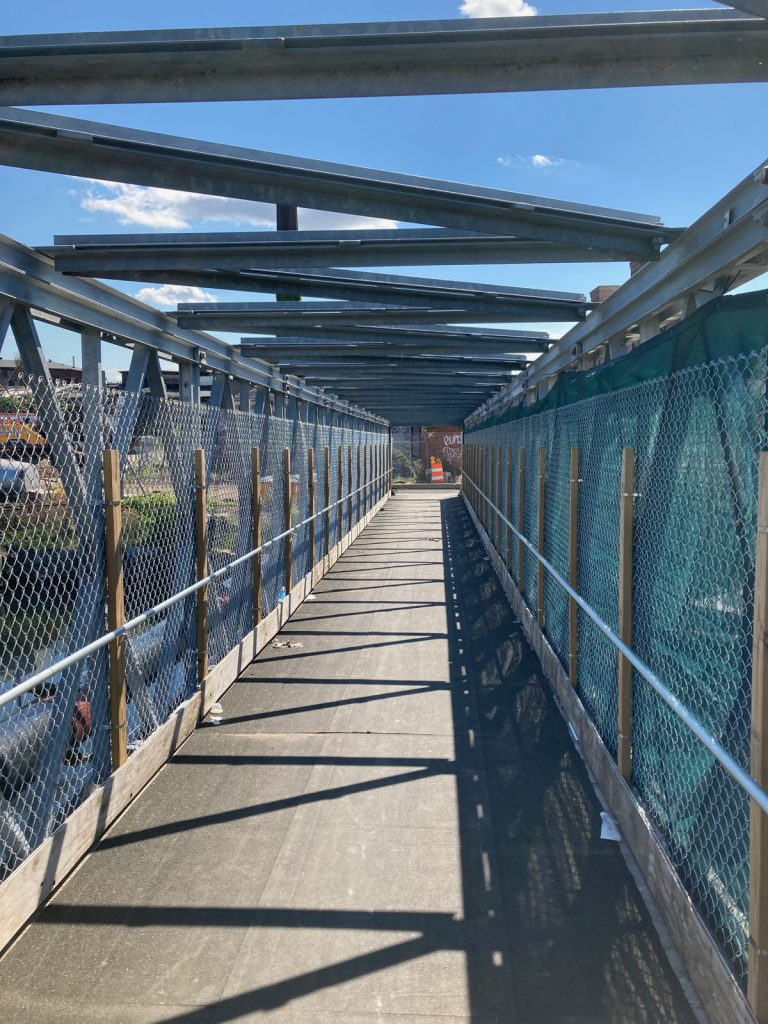 View along pedestrian bridge, there are metal beams and fencing on either side, and beams crossing the top of the bridge structure