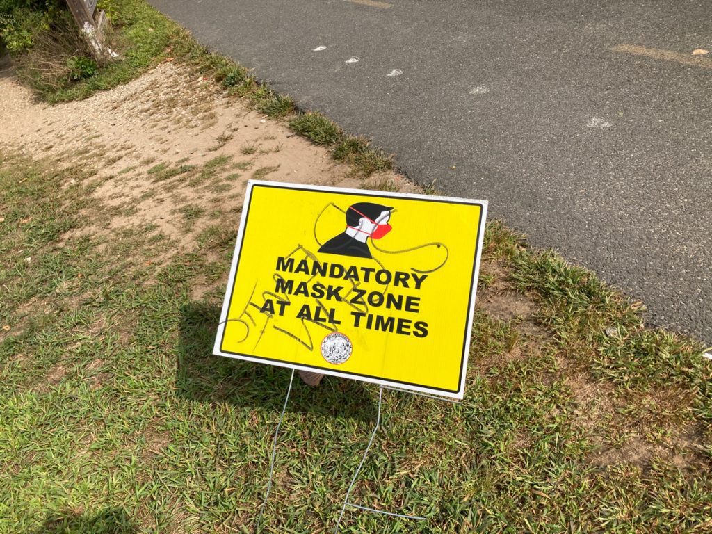"Yellow sign planted in grass next to pavement.  Black text on the sign reads ""Mandatory mask zone at all times""."