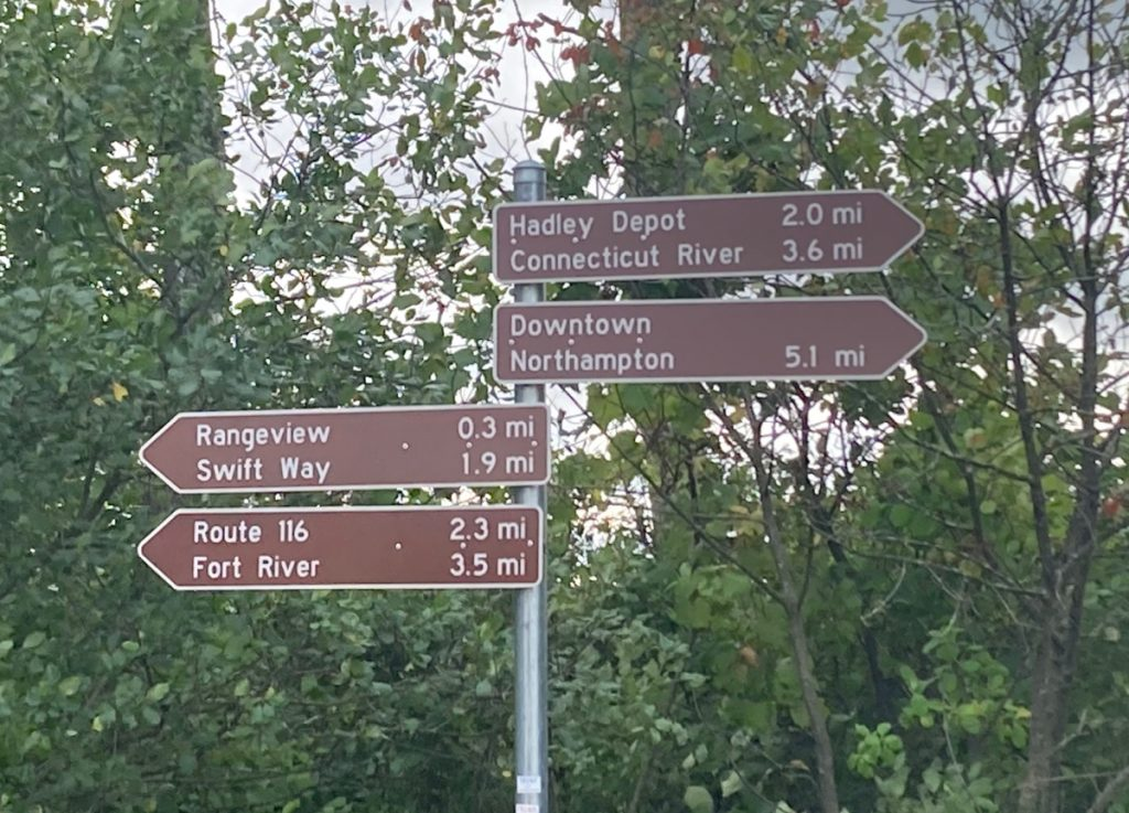 4 brown signs on a post, with white text indicating the distance and direction to several places, such as the Connecticut River, downtown Northampton, and the Fort River.