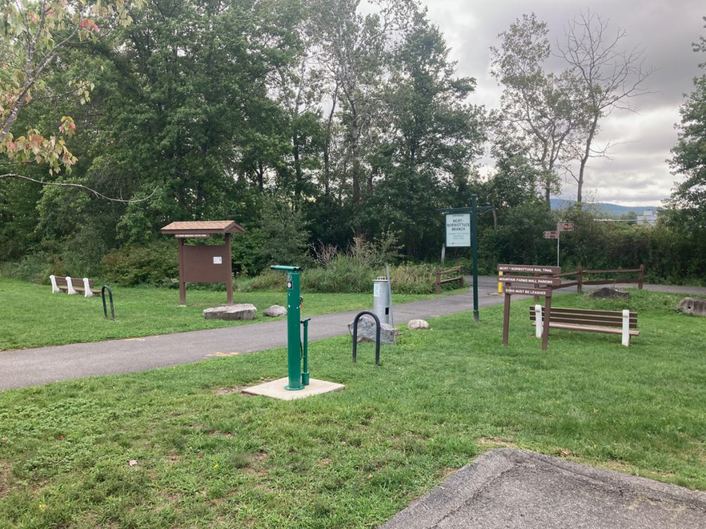 Paved trail piece connecting to main trail at right angle, with grassy area around it  There are some benches, bike racks, and a bike repair station.